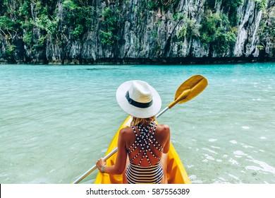 Woman paddling a kayak in the island lagoon between mountains. Kayaking in El Nido, Palawan, Philippines.