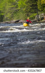 Woman paddling a solo canoe in whitewater