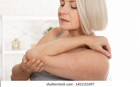 Woman with pain in arm, elbow. Pain in the human body, health care concept. Close up.