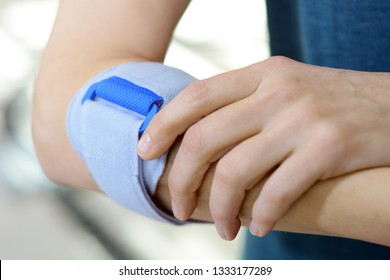 Woman with pain in arm or tendonitis is wearing sturdy orthosis as bandage