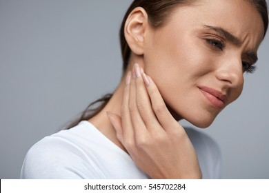 Woman In Pain. Closeup Of Beautiful Young Female Feeling Painful Toothache, Touching Face With Hand. Sad Stressed Girl Feeling Strong Teeth, Jaw Or Neck Pain. Dental Health And Care. High Resolution