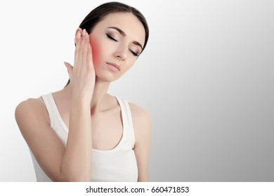 Woman In Pain. Closeup Of Beautiful Young Woman Feeling Painful Toothache, Touching Face With Hand. Sad Stressed Girl Feeling Strong Teeth, Jaw Or Neck Pain. Dental Health And Care. High Resolution