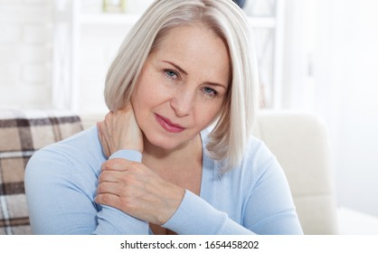 Woman with pain in her neck cloce up, medical shot at home. Concept photo with indicating location of the pain.