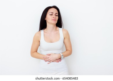 Woman with pain is holding her aching belly - isolated on white background