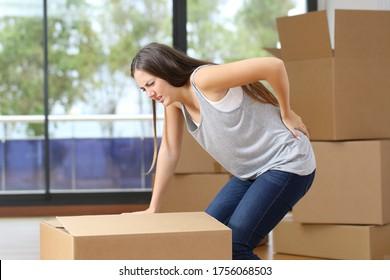 Mujer con dolor moviendo cajas con dolor de espalda agarrando área lumbar en casa