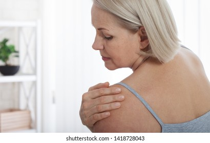 Woman with pain in shoulder. Pain in the human body,health care concept. Female holding hand to spot of neck.