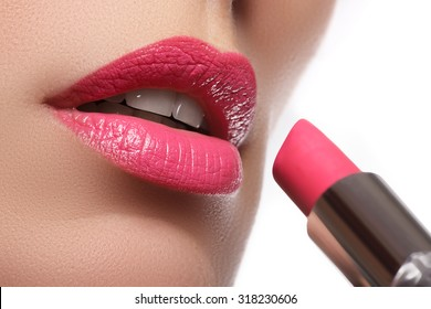 Woman painted pink lips. Beauty lips make-up. Perfect skin, full lips. Retro make up. Professional make-up artist applying sexy lips makeup. Fashion makeup