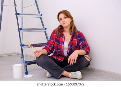 Woman painter sitting with brush in hand next to stepladder, white background