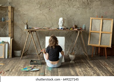 Woman painter sitting on the floor in front of an empty canvas and drawing. Art studio interior. Horizontal background. Drawing supplies, oil paints, artist brushes, canvas, frame. Creative concept