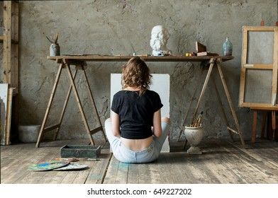 Woman painter sitting on the floor in front of an empty canvas and drawing. Art studio interior. Horizontal drawing background. Creative concept