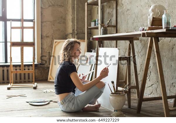 キャンバスの前の床に座って絵を描く女性の画家。アーティストのスタジオインテリア。図面用具、油絵の具、アーティストブラシ、キャンバス、枠。ワークショップまたはアートクラス。クリエイティブコンセプト