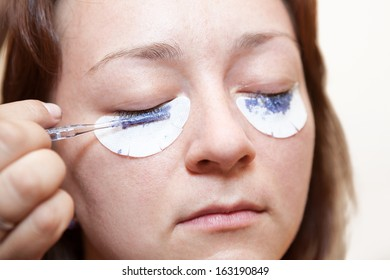 Woman painting with a brush his eyelashes. Permanent staining