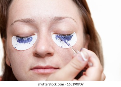 Woman painting with a brush his eyelashes. Chemical staining