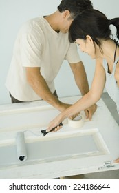 Woman painting door with paint roller, man protecting woodwork with masking tape