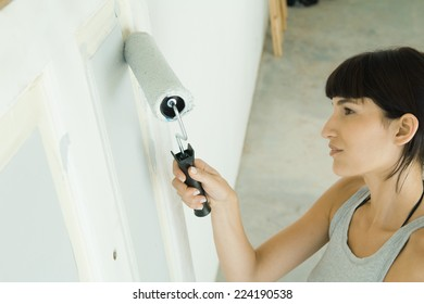 Woman painting door with paint roller