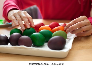Woman painting Easter egg in one color