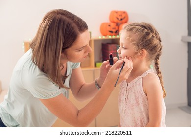 Woman painting face of her daughter for the Halloween celebration