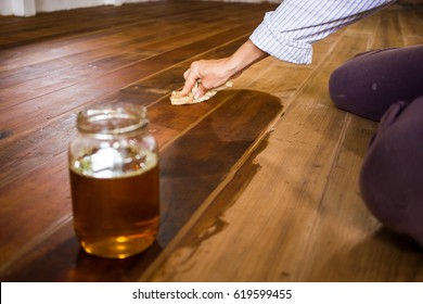 Woman painting floor with flax-seed oil