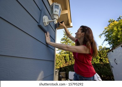 Woman Painting a House with blue paint. Horizontally framed photo.