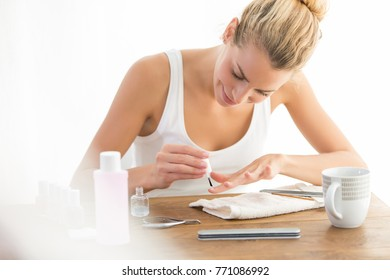 woman painting nails at home