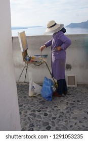 Woman painting  with oils in Santorini, Greece