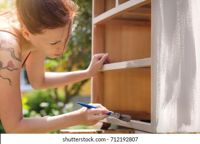 woman is painting an old dresser outdoor,  in white and grey shabby chic look