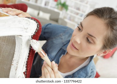 woman painting renewing chair at home