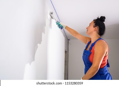 Woman at painting a room with paint roller