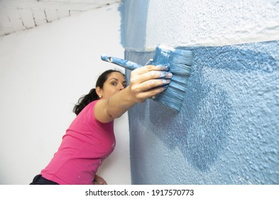 woman painting a wall of blue with a brush. Selective focus of the paintbrush