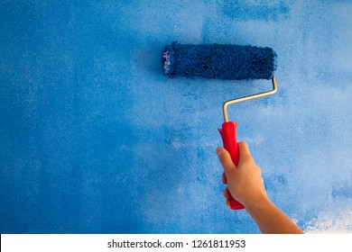 woman painting a wall with paint roller