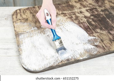 Woman painting wood.