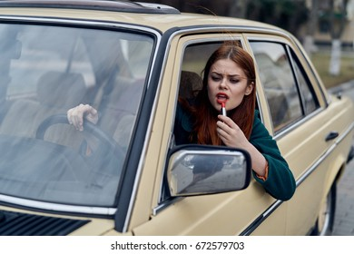 Woman paints her lips in the car