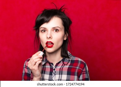 woman paints her lips with red lipstick, makeup, red background