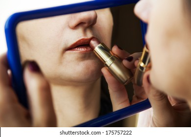 woman paints lips with lipstick before a mirror closeup