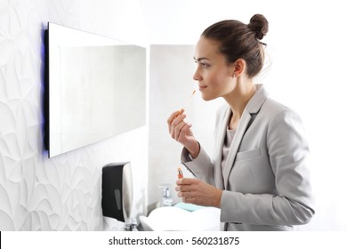 The woman paints lips in the office. Attractive business woman paints lips with lipstick in the company bathroom
