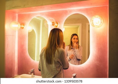 The woman paints lips in the toilet. Attractive happy woman applying makeup in the bathroom of a restaurant - Image