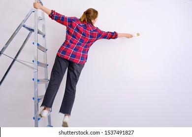 A woman paints the walls, falling from a stepladder. Problems with safety during repair work, copy space