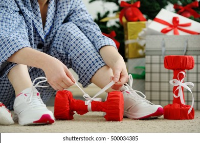 Woman in pajamas and athletic shoes unties the bow on the dumbbells. Christmas Present. Birthday Present.