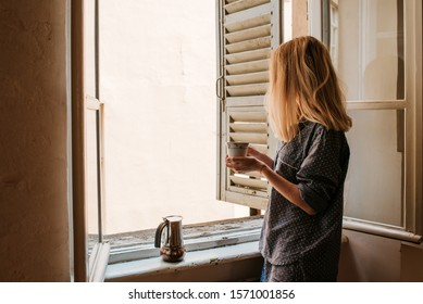 Woman in pajamas drinks morning coffee near window with shutters. Beginning of a new day. Hot drink after breakfast. Happy morning in Italy. Enjoy moment, relax lifestyle. Cozy sunnyday. Weekend vibes
