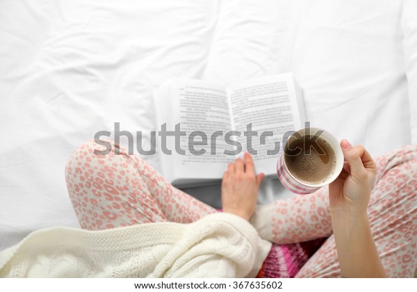 Woman in pajamas reading a book and drinking coffee on her bed