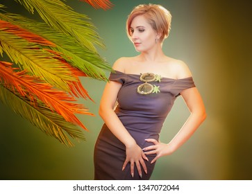 Woman in palm leaves. Rest in the southern countries. Travel in exotic countries. Touristic background. The girl with the sunny sedges. .