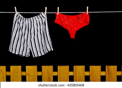 Woman panties and man underwear on clothesline on black background