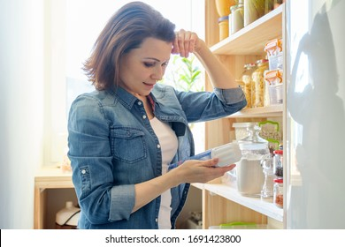Woman in pantry with groceries, wooden rack for storing food in the kitchen.