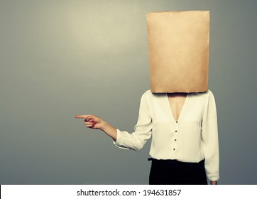 woman with paper bag on the head pointing at something over dark background