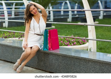 Woman with paper bags after shopping in summer city
