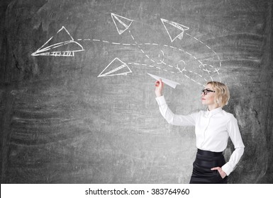 A woman with a paper plane ready to let it go. Side view. Blackboard with planes drawn on it at the background. Concept of starting a new project.