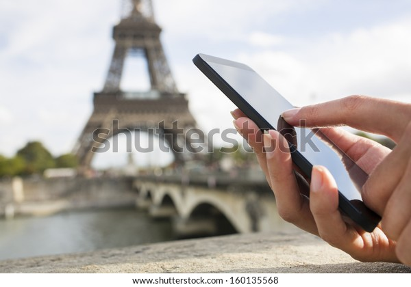 Woman in Paris using her cell phone in front of Eiffel Tower, seine bridge background, message sms e-mail