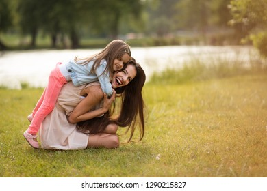 Woman in park having fun while carrying kid on her back