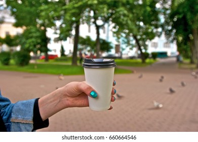 Woman in park holding white paper cup. Birds and trees in background.