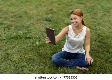 Woman in a park video chatting on tablet computer